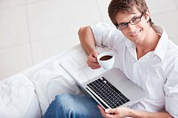 A young man with a cup and laptop
