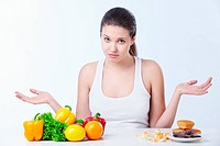 Doubting the girl with a healthy diet and sweet on a white background