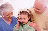 Girl using cell phone with grandparents
