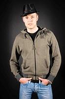 Junger Erwachsener Mann trägt Jeans und einen Kaputzenpullover und steht vor dunklem Hintergrund. Er steht lässig und mit verschränkten Armen und scha...