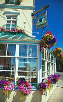 A view of the Swan Hotel in downtown Victoria showing hanging flower pots all around it