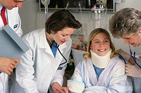 Doctors with teenage patient wearing neck brace