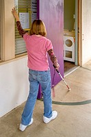 Using a white cane plus touch, a preteen girl finds her way at the Blind Children's Learning Center in Santa Ana, CA  Note hand on wall