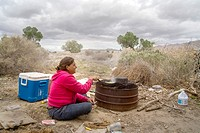 A homeless woman cooks corn on a primitive outdoor grill a primitive outdoor encampment in the desert town of Victorville, CA
