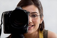 Close_up of a smiling young woman taking a photograph