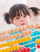 Portrait of baby girl 12_17 months playing with abacus