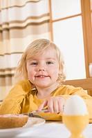 Girl spreading jam on bread, smiling, portrait