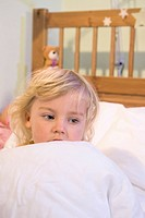 Girl covered with blanket on bed, close up