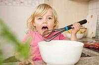 Girl preparing cake, tasting batter