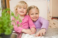 Girls rolling dough on kitchen worktop, smiling, portrait (thumbnail)