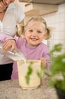 Mother and daughter pouring milk into measuring cup (thumbnail)