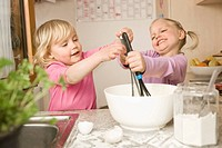 Girl mixing batter in bowl, smiling