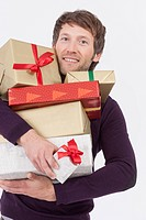 Mid adult man with Christmas gifts, smiling, portrait (thumbnail)