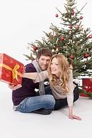 Woman reaching Christmas gift to man, smiling