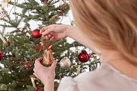 Mid adult woman positioning christmas bell on tree
