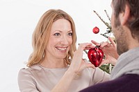 Woman showing red heart shaped Christmas ornament to man, smiling