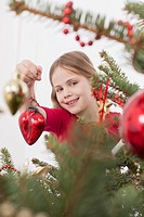 Girl showing heart shaped Christmas bauble, smiling, portrait