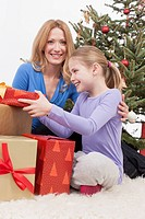 Mother and daughter sitting with Christmas gifts, smiling