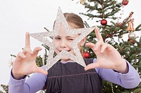 Girl winking through silver star shaped Christmas ornament, smiling, portrait