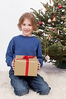 Boy holding Christmas gift, smiling, portrait