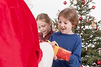Santa Claus giving gift to boy and girl