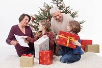 Grandparents with grandchild sitting with Christmas gift, smiling