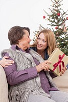 Senior woman and mid adult woman smiling with Christmas gift