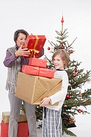 Boy holding Christmas gifts while senior woman adjusting, smiling