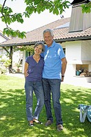 Germany, Bavaria, Senior couple standing in yard, smiling