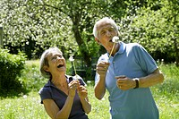 Germany, Bavaria, Senior couple blowing blowball