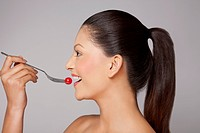 Side view of a woman eating cherry tomato on fork