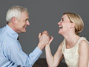 Mature couple arm wrestling, smiling