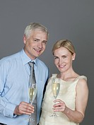 Mature couple drinking sparkling wine, smiling, portrait