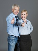 Mature couple showing thumbs up, smiling, portrait