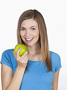 Young woman holding apple, smiling, portrait
