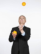 Mature man juggling with oranges