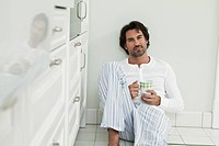 Germany, Berlin, Mature man with coffee cup in kitchen, portrait