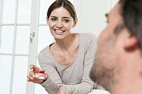 Germany, Berlin, Man looking at woman holding cake