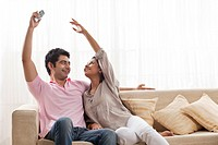 Young woman trying to reach remote control from man