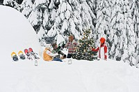 Austria, Salzburg, Men and women sitting by christmas tree in winter