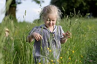 Germany, Bavaria, Girl walking through spring meadow, boy in background