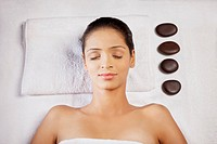 Close_up of young woman lying on massage table with pebble stones on side