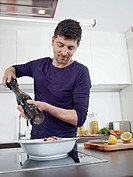 Germany, Cologne, Mid adult man cooking food in kitchen