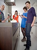 Germany, Cologne, Men and women drinking wine in kitchen