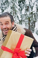 Austria, Salzburg County, Mature man standing with christmas parcel, smiling, portrait (thumbnail)