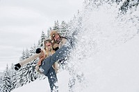 Austria, Salzburg County, Couple splashing snow in snowy landscape,smiling