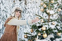 Austria, Salzburg County, Mid adult woman lighting candle on Christmas tree, smiling, portrait