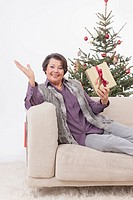Senior woman sitting on couch with christmas gift, smiling, portrait