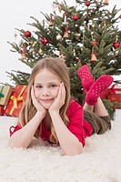 Girl lying on fur carpet, christmas tree and gifts in background