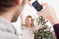 Mid adult man taking photograph of woman, smiling